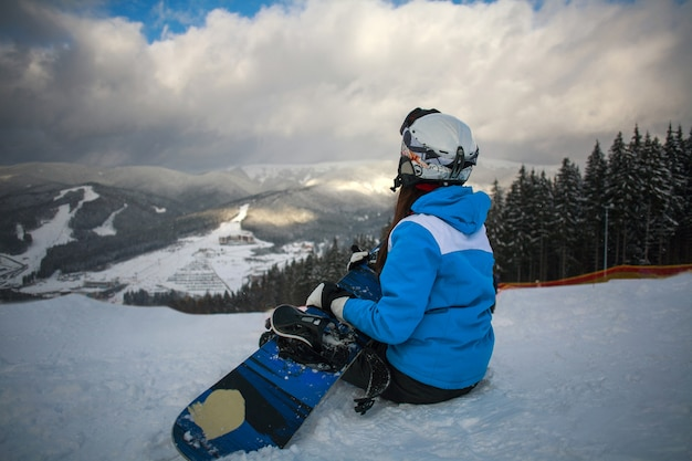 冬のスキーリゾートで女性スノーボーダーが座っています。