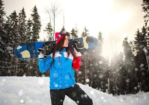 松林の冬の降雪でスノーボードを持つ意図的な女性