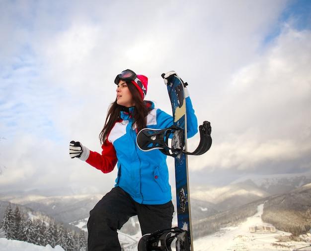 冬のスノーボーダーの女の子は空の山の頂上に手を伸ばす