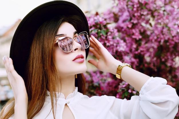 Девушка в солнечных очках держит шляпу возле цветущих деревьев