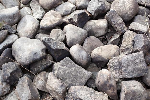 灰色の石のクローズアップ。石のテクスチャ。散乱した灰色の玉石。上記の石の道の背景。砂利。
