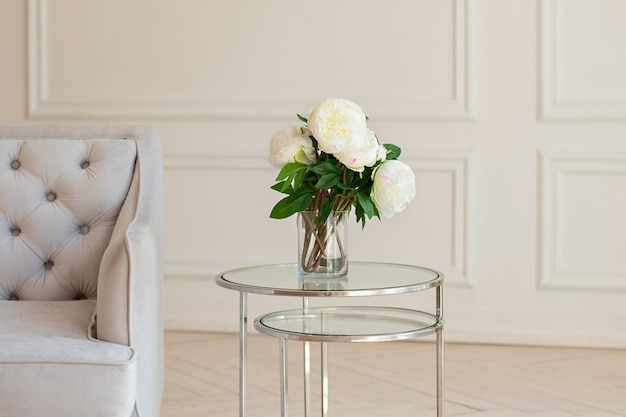 リビングルームの灰色のソファーの近くのテーブルに美しい牡丹の花と花瓶。居心地の良い家の装飾、白い部屋のコーヒーテーブルに新鮮な白い牡丹。