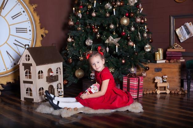 Счастливого рождества, веселых праздников. маленькая девочка в красном винтажном платье сидит возле украшенной елки с деревянной игрушкой щелкунчик. семейный отдых. счастливый малыш наслаждается праздником.