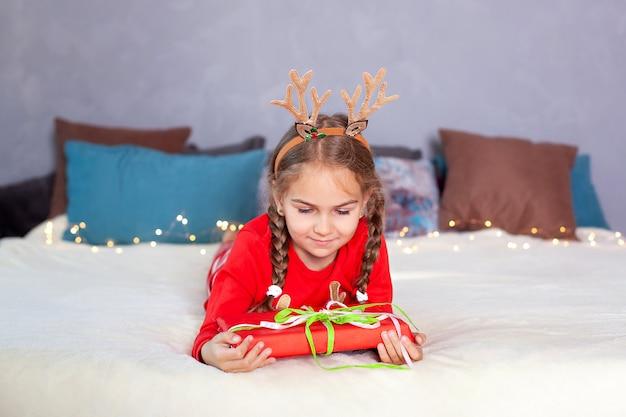 メリークリスマス。新年。クリスマスギフトボックスとおさげの幸せな笑みを浮かべて少女。赤いパジャマを着て、頭に鹿の角のある子供はクリスマスイブにベッドに横になり、自宅で贈り物を開きます。