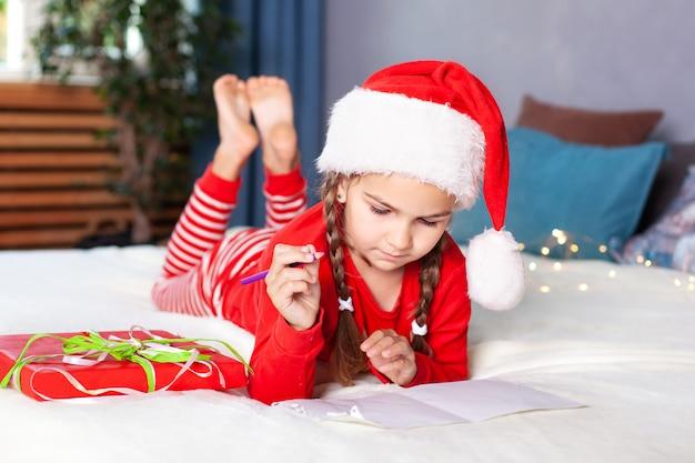 Празднование рождества. новый год! маленькая девочка пишет письмо деду морозу в спальне