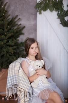 白いドレスを着た金髪の少女は、テディベアと夢の抱擁で椅子に座っています。居心地の良い家。自然と調和したエコスタイルの部屋。クリスマスの雰囲気、快適さ。