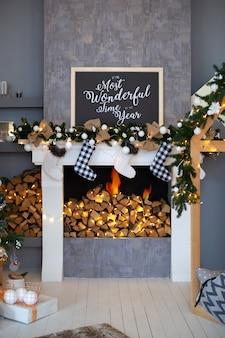 クリスマスのストッキングと部屋のインテリアにプレゼントが付いている暖炉。白い暖炉は、リビングルームのクリスマスの装飾で飾られています。クリスマスイブに暖炉に空のストッキングがかかった。