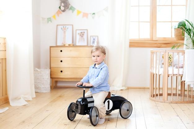 小さな男の子。おもちゃのビンテージ車に乗って幸せな子。自宅で遊んで面白い子供。夏と旅行のコンセプト。保育園で車のペダルを運転するアクティブな少年。レトロな車、おもちゃの車の中で少年を運転する幼児
