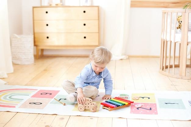 少年は木製の車で遊ぶ。子供のための教育の木のおもちゃ。北欧風の子供部屋の床に座っている少年の肖像画。エコ玩具、子供部屋の装飾