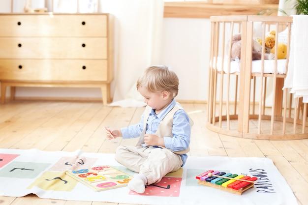 少年は家で木のおもちゃで遊ぶ。子供のための教育の木のおもちゃ。北欧風の子供部屋の床に座っている少年の肖像画。エコ玩具、子供部屋の装飾