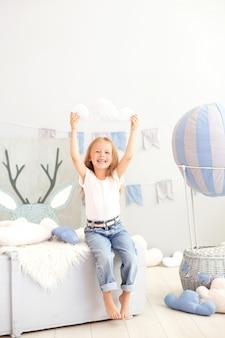 カジュアルな服装の少女は、装飾的な風船の雲枕を保持しています。子供は子供部屋で遊ぶ。幼年期の概念。誕生日、休日の装飾