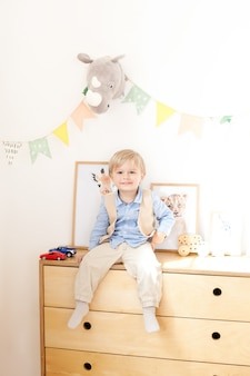 Маленький мальчик сидит на комоде возле белой стены с флагами и игрушками. портрет мальчика, сидящего в детской комнате в скандинавском стиле. экологически чистый декор детской комнаты