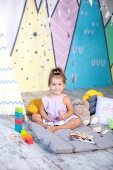 Девочка играет вигвам. скандинавский интерьер и текстиль для детской. счастливый малыш играет в палатке в детской комнате. маленькая девочка играет в детском саду. концепция детства, развитие ребенка.