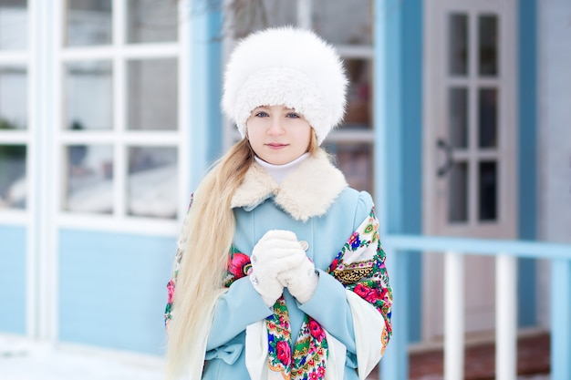 青いコート、白い毛皮の帽子、冬のスカーフでかわいいブロンドの女の子。家のポーチの女の子。冬の家。路上でポーズをとるモデル。冬の休日の概念。ロシアの塗装ショール