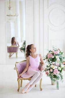 Милая балерина в розовой пачке и в пуантах сидит в кресле. девушка изучает балет.