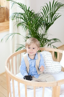 小さな男の子。ベビーベッドで遊んで幸せな少年の肖像画。少年は保育園のベビーベッドに一人で座っています。孤独な赤ちゃんはベビーベッドに滞在します。ワイフ子。ベッドの子供は笑っています。インテリアの子供部屋。