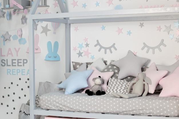 白い日当たりの良い寝室に子供用ベッド。子供部屋とインテリアデザイン。自宅での赤ちゃんや幼児の男の子のためのベッド。子供の保育園の寝具と織物。昼寝と睡眠時間。枕付きの子供用ベッドルーム。