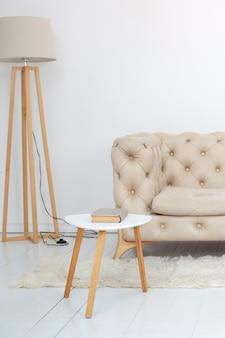 居心地の良いリビングルームのインテリアの床にコーヒーテーブルとランプのあるベージュのソファ。白い壁にソファ。北欧スタイルのリビングルームのインテリア。ロビー。カントリーハウスの部屋のインテリア。