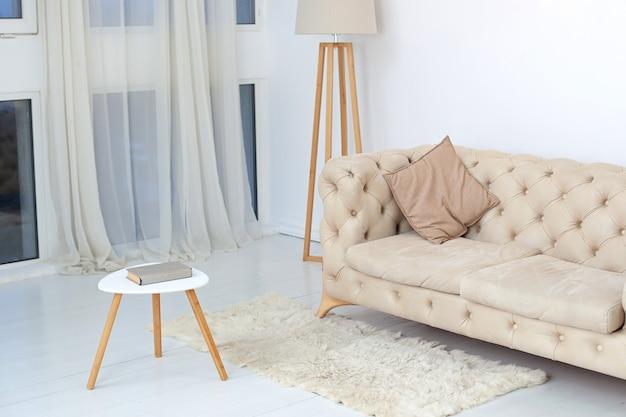 広々とした白いリビングルームにある、装飾的な枕、コーヒーテーブル、ランプを備えたベージュのソファ。大きな窓の近くにある快適なソファのある広々とした部屋のインテリア。快適さの概念。室内装飾