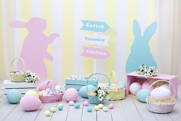 イースター!バニーとバスケットが付いた多くのカラフルなイースターエッグ!部屋のイースター装飾、ゲーム用の子供部屋。ニンジンとウサギのバスケット。イースターの写真撮影。巣、卵、干し草の箱。