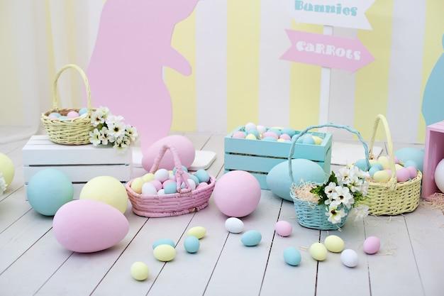 イースター!バニーと花のバスケットが付いた多くのカラフルなイースターエッグ!イースタールームの装飾と装飾、子供用プレイルーム。大小の塗装イースターエッグとカラフルなウサギ。室内装飾