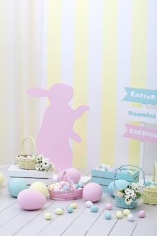 イースター!バニーと花のバスケットが付いた多くのカラフルなイースターエッグ!イースタールームの装飾と装飾、子供用プレイルーム。カラフルな塗装イースターエッグとカラフルなウサギ。家の装飾を祝う