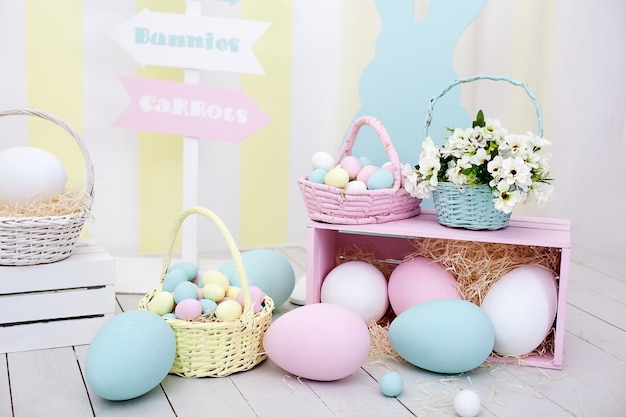 イースター!バニーと花のバスケットが付いた多くのカラフルなイースターエッグ!イースタールームの装飾と装飾、子供用プレイルーム。カラフルな大小の塗装イースターエッグとカラフルなウサギ。