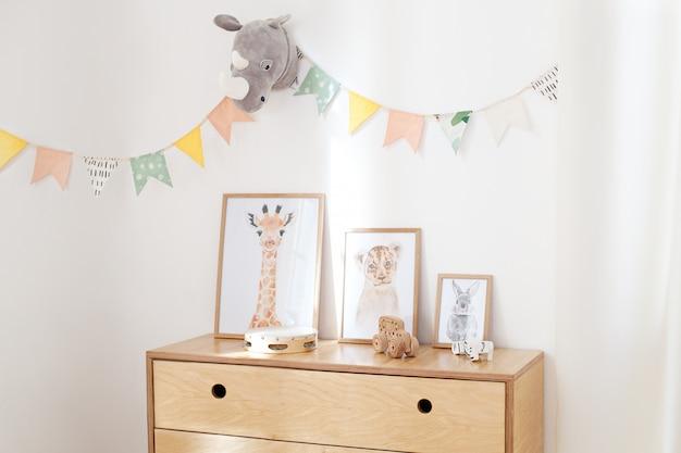 Деревянные эко игрушки в детской комнате, постеры, рамы, деревянный комод и белая стена с праздничными флагами, интерьер детской спальни. белая стена украшена флагами в детском саду
