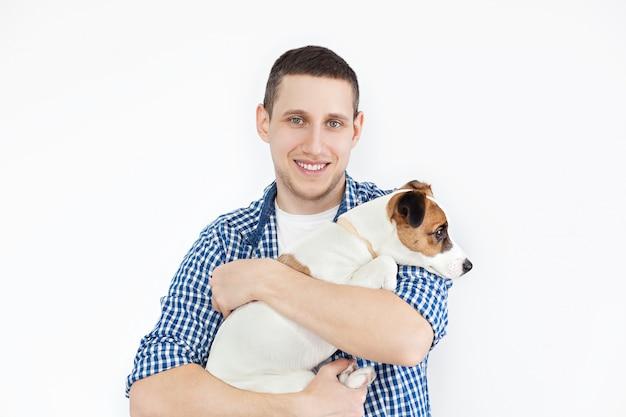 純血種の犬を保持している笑顔のハンサムな男