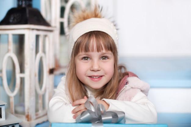 Счастливого рождества, веселых праздников! поверхность. портрет маленькая милая девушка в шляпе, сидя на крыльце дома зимой. ребенок сидит на деревянной лестнице на террасе. сочельник. ребенок открывает поверхностный подарок.