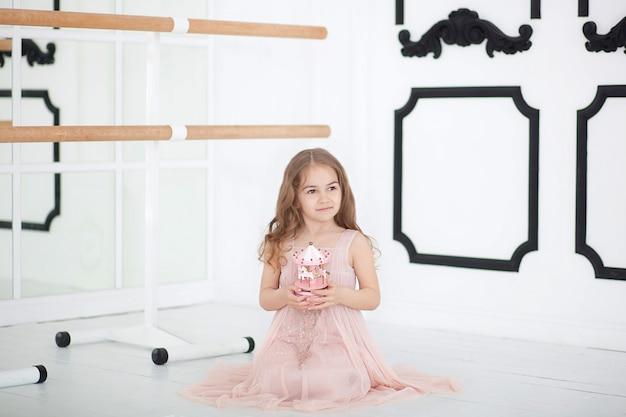 ドレスを着た小さなバレリーナが床のダンスクラスに座っています。音楽グッズカルーセルを保持している少女。子供は贈り物を受け取ります。ヴィンテージ音楽カルーセルグッズ。屋内バレエホールクラスルーム