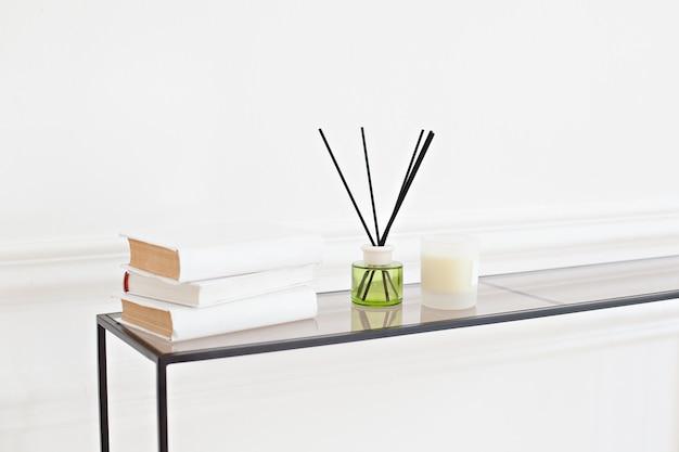 白い壁の部屋のテーブルのリードディフューザー。リビングルームの便器にキャンドルで手作りのリード芳香剤。北欧の家の装飾:キャンドル、アロマディフューザー、スパサロンの本。モダンな家の装飾