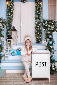 Счастливого рождества, веселых праздников! поверхность. маленькая девочка стоит возле почтового ящика во дворе дома зимой. девушка отправила письмо деду морозу со списком рождественских подарков. ребенок отправляет сообщение на северный полюс.