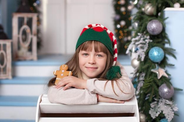 メリークリスマス、ハッピーホリデー! 。手でクッキーとクリスマスのエルフの衣装での幸せな女の子。子供はサンタクロースのジンジャーブレッドマンを保持しています。帽子の陽気なエルフの肖像画。