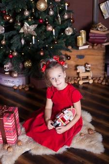 , счастливого рождества, веселых праздников. маленькая девочка в красном платье держит винтажную деревянную игрушку щелкунчика около классической рождественской елки дома. балерина с щелкунчиком на поверхности евы.