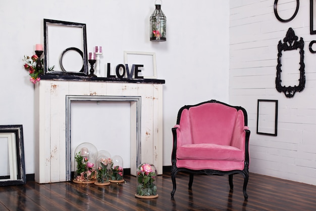 明るい部屋と人工暖炉のあるビンテージアームチェア。木製の白い壁とインテリアの屋根裏部屋。壁の写真フレーム。あなたが人を置くことができるスペース。ゴシック様式の部屋。