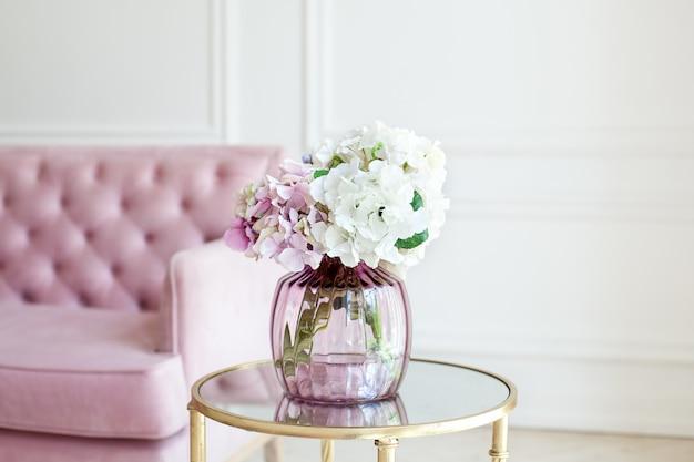 ガラスの花瓶にパステル調のアジサイの花束。自宅の花瓶の花。紫陽花の美しい花束は、白いリビングルームのピンクのソファの近くのテーブルの上の花瓶にあります。ホームインテリア。スカンジナビア