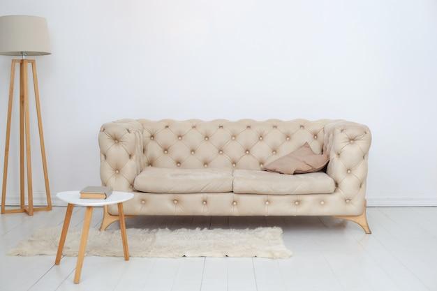 広々とした白いリビングルームにある、装飾的な枕、コーヒーテーブル、ランプを備えたベージュのソファ。白い壁に快適なソファを配した広々とした室内。室内装飾。北欧スタイル