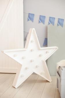 Звездная лампа на полу серой стены с праздничными флагами. большая звезда с лампочками. современные предметы интерьера. декоративная звезда с лампами. звездообразные белые светодиодные фонари с одиночной рамой