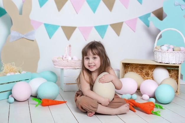 イースター!イースターのカラフルな卵、イースターバスケット、ノウサギと白の美しい少女。イースターの装飾、春の装飾の家。家族の休日、伝統。収穫、小さな農家。