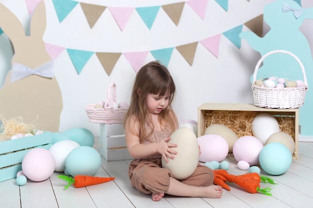 イースター!オーバーオールの少女は大きなイースターエッグと一緒に座っています。イースターの場所、装飾。家族の休日、伝統。カラフルな部屋。小児発達。イースター装飾。子供は保育園で遊ぶ