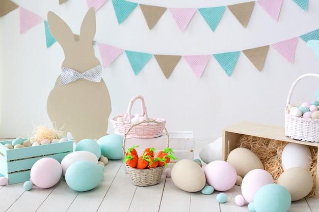イースター!たくさんのカラフルなイースターエッグ!ウサギと卵のバスケットが付いている部屋のイースター装飾。ファーム。収穫。ニンジンとバニーのバスケット。イースター装飾。白い壁に休日フラグ