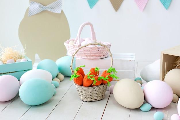 イースター!たくさんのカラフルなイースターエッグ!ウサギと卵のバスケットが付いている部屋のイースター装飾。ファーム。収穫。ニンジンとイースターのウサギのバスケット。イースター装飾。壁にホリデーフラグ