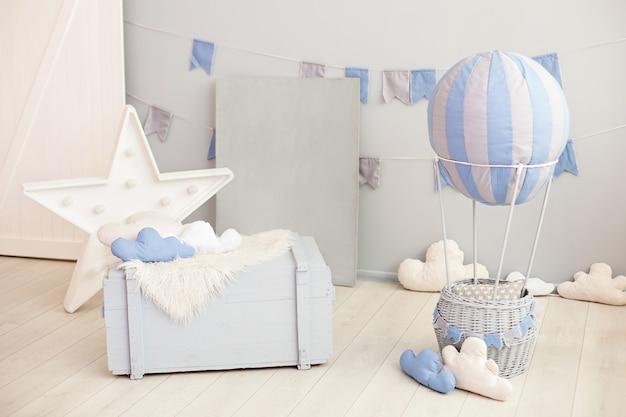 木製のたんすとお祝いフラグと白い壁に雲と風船を持つ子供のためのモダンなビンテージルームインテリア。子供の寝室。幼稚園のインテリア。素朴な