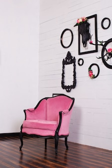 明るい部屋でビンテージベロアアームチェア。頭蓋骨と木製の壁に掛かっている角を持つさまざまな空の写真フレーム。壁の装飾の概念。インテリア、ヴィンテージ、モダン、ロフト。ゴシック様式