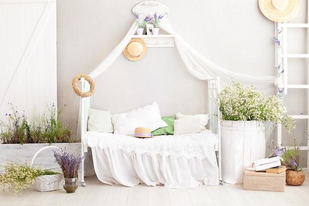 プロヴァンス、素朴なスタイル!カントリーハウスのぼろぼろの白いシックな寝室のインテリア。ラベンダーの花瓶、ヒナギクの樽、村の家の白いベッド。プロヴァンスのインテリアアイテム。ハイキー