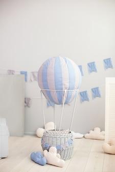 Яркая детская комната с воздушным шаром, воздушными шарами и текстильными облаками на белой стене с праздничными флагами. детская спальня. интерьер детского сада. скандинавский интерьер комнаты. деревенский декор