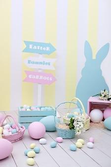 イースター!バニーと花のバスケットが付いた多くのカラフルなイースターエッグ!ゲームのための子供部屋、家族の休日。春とイースターの部屋の装飾。カラフルなイースターの部屋のインテリア。カラフルなバニー