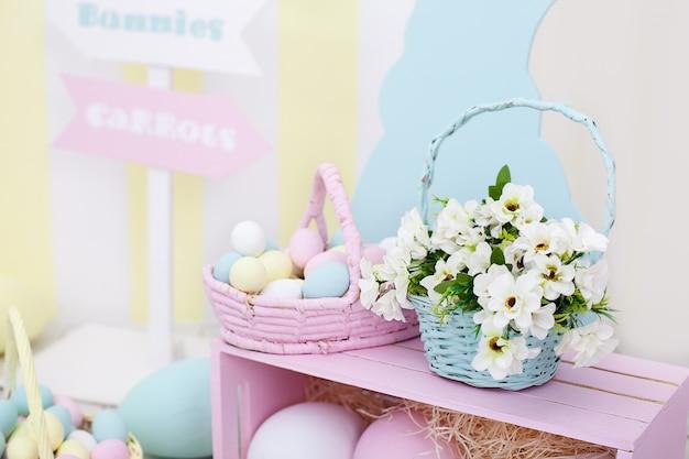 イースター、おめでとう!イースターの大きなカラフルなバスケットには、卵と春の花が描かれています。イースターバニーと大きなカラフルな卵。春の部屋の装飾とイースターの装飾。春の家の装飾と春の花。