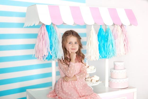 お菓子とテーブルの上に座って美しい少女。キャンディの誕生日バー。赤ちゃんの顔のクローズアップの肖像画。家でコーヒーメーカーと遊ぶかわいい女の子。キャンディー装飾の子供部屋。お誕生日